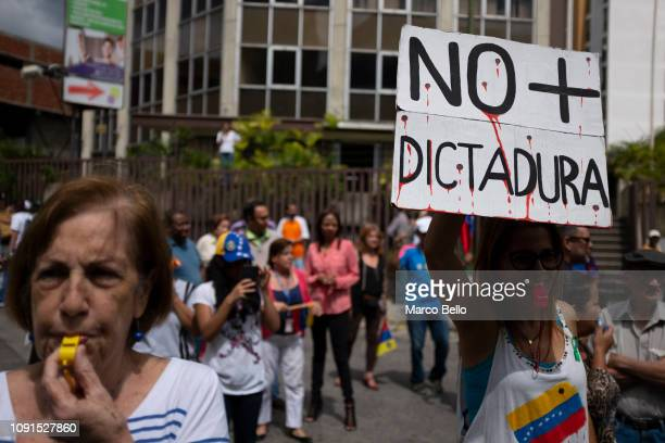 A woman holds a banner that reads No more dictatorship during a demonstration against the government of President Nicolás Maduro called by the...