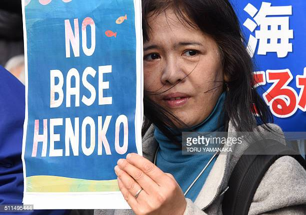 A woman holds a banner while listening to a speaker during a rally against a new US military base in Okinawa Japan's nouthernmost prefecture in front...