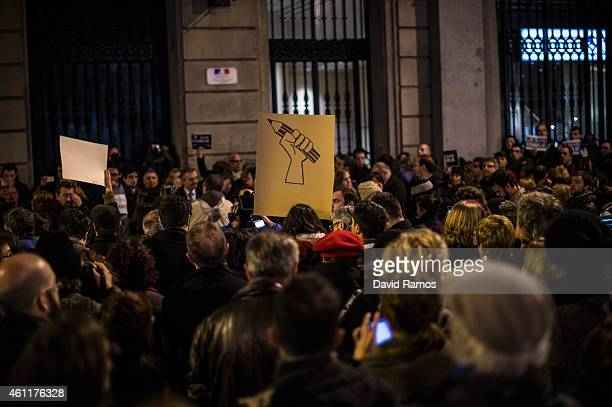 Woman holds a banner with a pencil painted during a gathering of people showing their support for the victims of the terrorist attack at French...