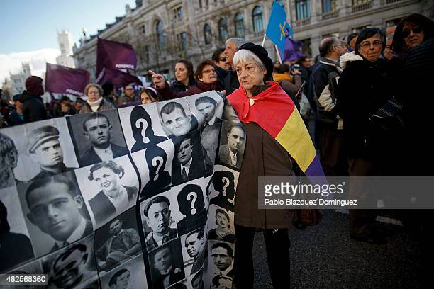 A woman holds a banner with portraits of victims of the Spanish Civil War during a march of Podemos political party on January 31 2015 in Madrid...