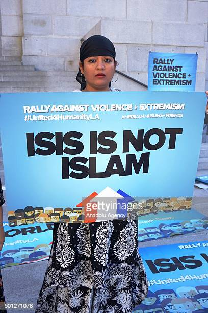 A woman holds a banner written 'ISIS is not Islam' on it as hundreds of Californians mostly including Muslims gathered during a protest against...