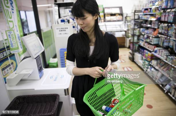 A woman holds a basket of items after paying for them at an unmanned cash register during a demonstration at a FamilyMart UNY Holdings Co FamilyMart...
