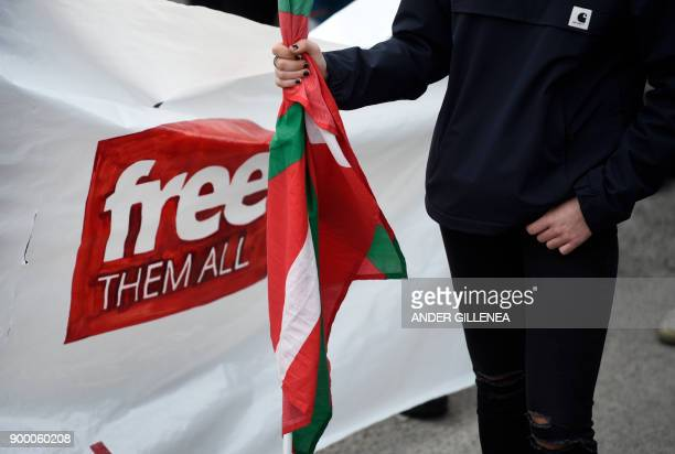 A woman holds a Basque flag as people gather outside the Martutene prison in San Sebastian during a demonstration demanding the release of prisoners...