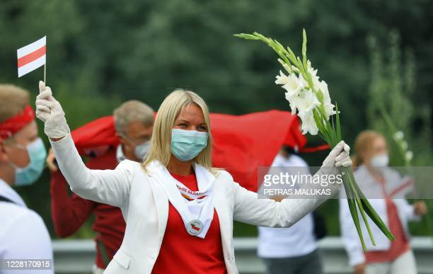 A woman holds a Belarussian opposition flag and flowers as people form a human chain from Vilnius to Medininkai along the border with Belarus to show...