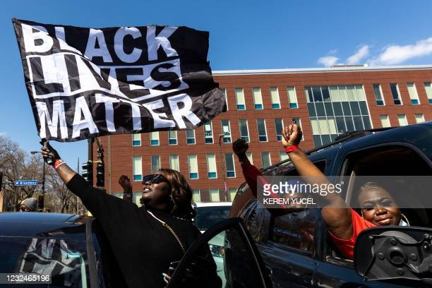 Woman holds a Black Lives Matter flag during the funeral service of Daunte Wright outside the Shiloh Temple International Ministries in Minneapolis,...