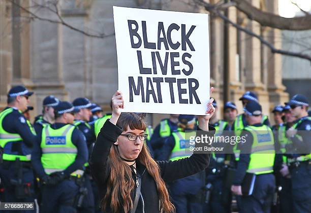 A woman holds a Black Lives Matter placard aloft as Australian police offcers look on during a rally to support the Black Lives Matter movement on...