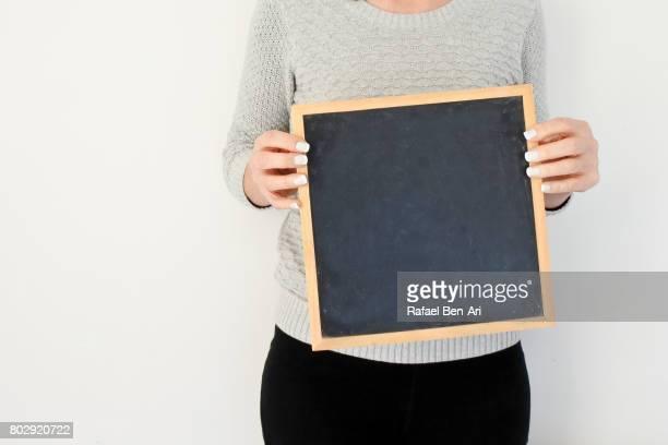 Woman holds a blank blackboard