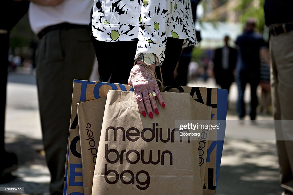 A woman holds a Bloomingdale's department store shopping bag as she waits to cross the street in a retail area known as the 'Magnificent Mile' in Chicago, Illinois, U.S., on Tuesday, June 11, 2013. Sales at U.S. retailers probably rose in May as an improving job market gave consumers the confidence to shop for automobiles, home furnishings and clothing, economists said before reports this week. Photographer: Daniel Acker/Bloomberg via Getty Images