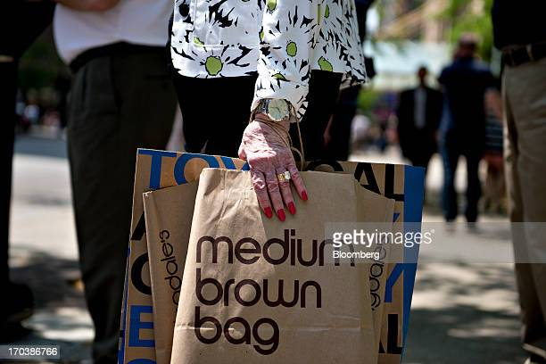 A woman holds a Bloomingdale's department store shopping bag as she waits to cross the street in a retail area known as the 'Magnificent Mile' in...