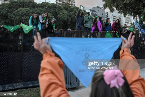 A woman holds a blue headscarf against the legalization of abortion in front of demonstrators with green headscarves in its favor outside the...