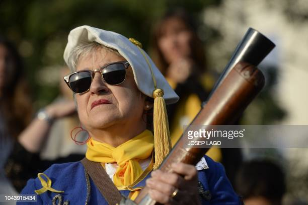 A woman holds a blunderbuss gun in Sant Julia de Ramis near Girona on October 1 2018 during a ceremony to commemorate the anniversary of a banned...