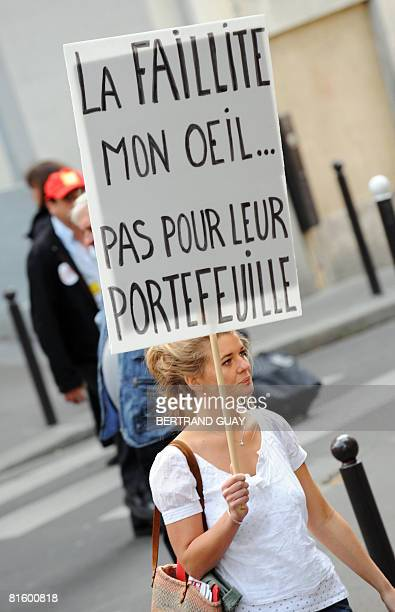 A woman holds a board reading 'Bankruptcy My foot Not for their wallet' as she demonstrates as part of a nationwide strike called by the two biggest...