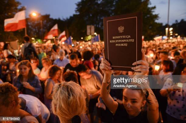 A woman holds a book with it's cover reading The Constitution of the Republic of Poland during a protest against Polish government proposing laws...