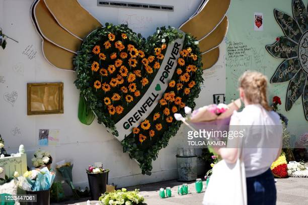 Woman holds a bouquet of flowers as she looks at a memorial to the victims of the Grenfell Tower fire, in west London on June 14 four years after the...
