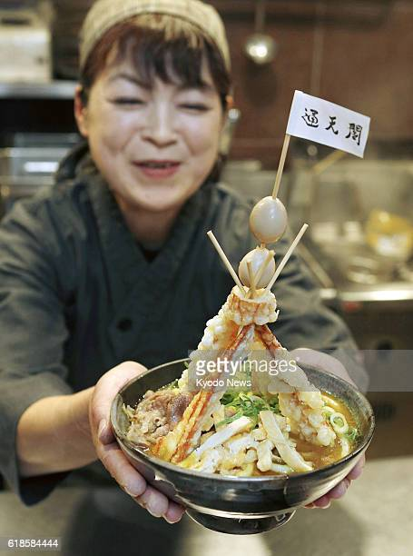 A woman holds a bowl of 'Tower Curry Udon' noodles at a restaurant inside ShinImamiya Station of Nankai Electric Railway Co in Osaka on Oct 27 ahead...