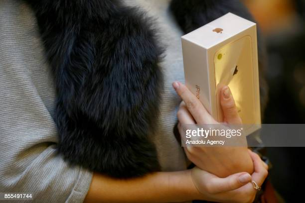 A woman holds a box of Apple phone in her hand after Apple launched iPhone 8 and 8 plus at the GUM department store in Moscow Russia on September 29...