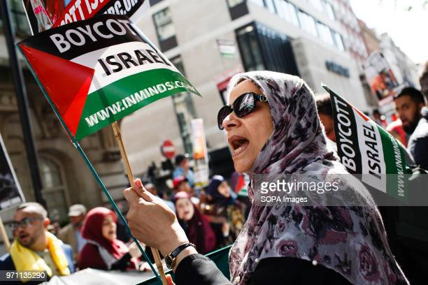 A woman holds a 'Boycott Israel' flag during the annual proPalestine/antiIsrael Al Quds Day demonstration in central London The demonstration is...