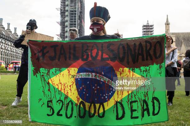Woman holds a Brazilian flag painted with text criticising President Jair Bolsonaro's handling of the Covid-19 pandemic in Brazil during a protest in...