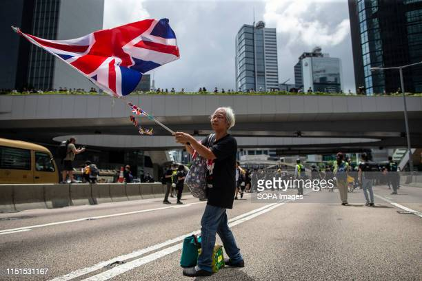 A woman holds a British flag during a demonstration in Hong Kong Thousands of protesters have occupied the roads near the government headquarters and...