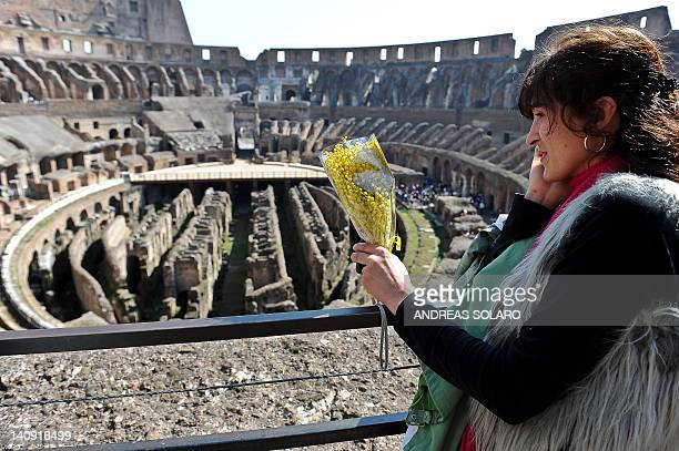 A woman holds a bunch of mimosa as she visits Rome's Colosseum to celebrate the International Women's Day on March 8 in Rome The entrance of the...