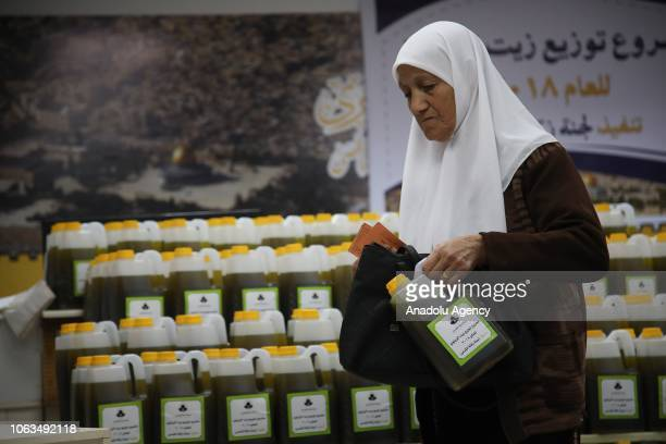 A woman holds a can of olive oil at a facility after being picked from an olive tree to distribute to the ones in need at the Masjid alAqsa Compound...