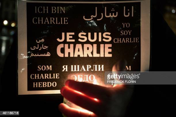 """Woman holds a candle and a poster reading """"I am Charlie"""" during a gathering in Strasbourg, eastern France, on January 8 a day after a deadly attack..."""