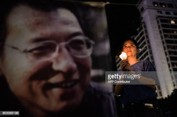 A woman holds a candle as she attends a vigil for terminallyill Nobel laureate Liu Xiaobo in Hong Kong on June 29 2017 Liu wants Chinese authorities...