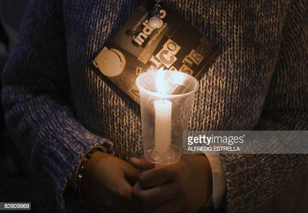 A woman holds a candle during a demonstration against the increasing insecurity and wave of kidnappings on August 30 in Mexico City People form all...