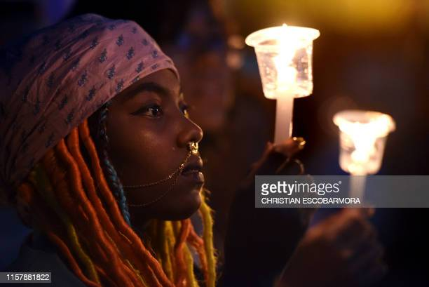 TOPSHOT A woman holds a candle during a protest against the murder of social leaders and exFARC guerrillas in Cali Colombia on July 26 2019