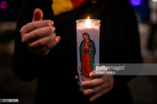 A woman holds a candle during a protest in front of the US embassy in Mexico City on June 4 over the death of George Floyd in police custody in...