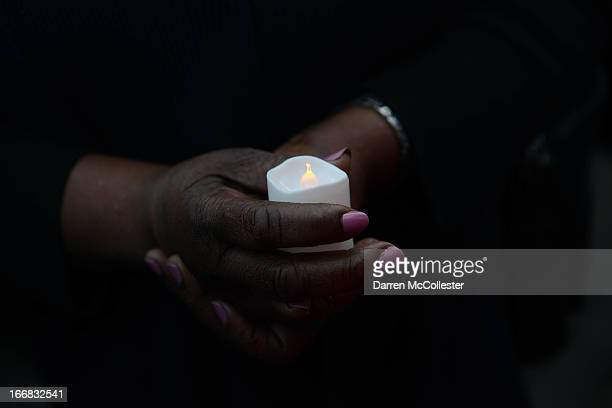 A woman holds a candle during a vigil held by the city of Cambridge and the Cambridge Black Pastors' Association to show support for those affected...