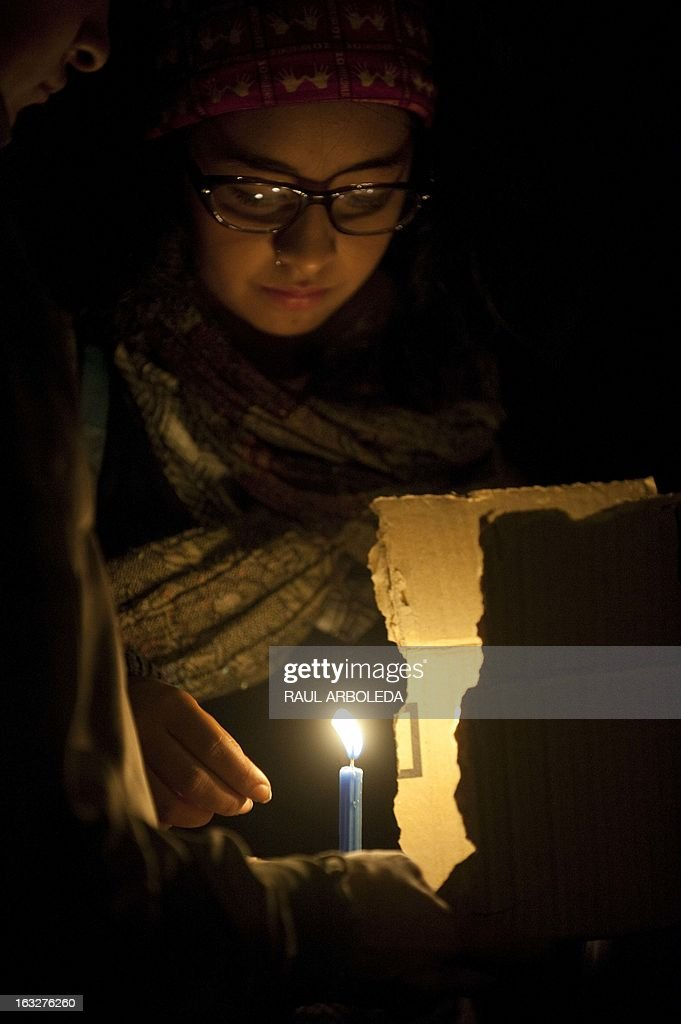 A woman holds a candle outside the Venezuelan embassy in Bogota, Colombia on March 6, 2013, after Venezuelan President Hugo Chavez's death. The flag-draped coffin of Venezuelan leader Hugo Chavez was borne through throngs of weeping supporters on Wednesday as a nation bade farewell to the firebrand leftist who led them for 14 years. AFP PHOTO / Raul ARBOLEDA