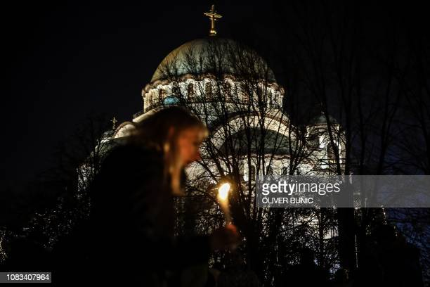 A woman holds a candle passing by the Church of Saint Sava during a silent march in Belgrade in memory of Serb politician Oliver Ivanovic murdered a...