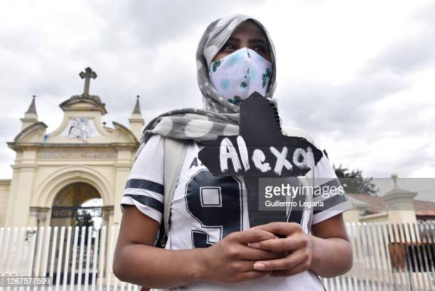 Woman holds a cardboard cross with the name of a murdered young woman during a protest triggered by recent massacres in Samaniego and Cali on August...