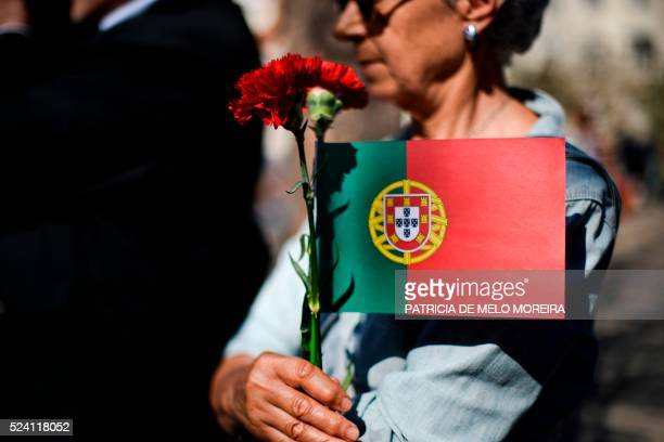 A woman holds a carnation a symbol of the 1974 Portuguese revolution and the Portuguese flag in central Lisbon on April 25 during a rally to...