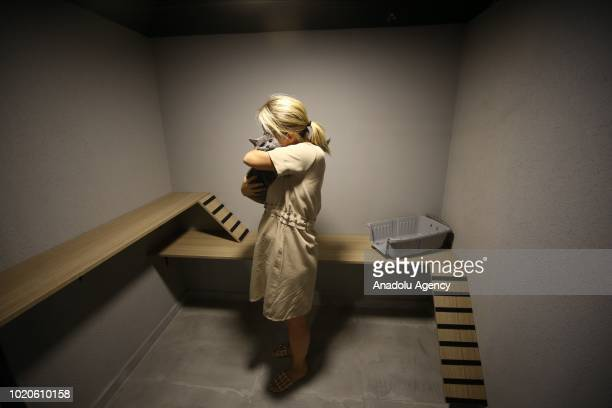 A woman holds a cat in room at a Cat Pet Hotel in Bursa Turkey on August 21 2018 Hotel has total of 32 separate standard luxury and suit rooms for...