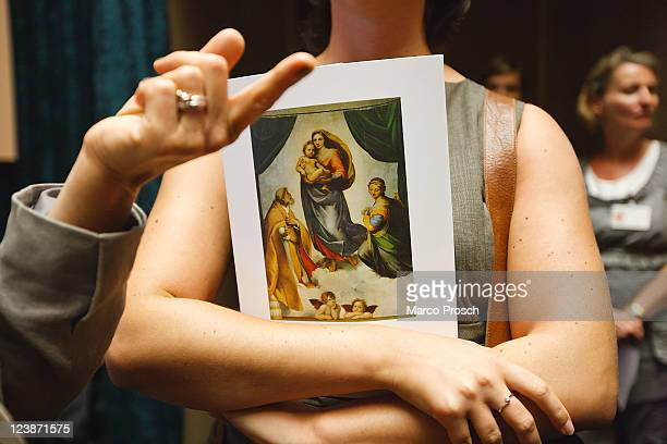 Woman holds a catalog of the exhibition 'Himmlischer Glanz' with Raffaelo 'Raffael' Santi's paintings 'The Sistine Madonna' and 'Madonna Di Foligno'...