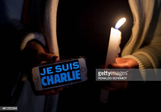 A woman holds a cellphone reading 'Je Suis Charlie' in support of the victims of the terrorist attack at the French magazine Charlie Hebdo on January...