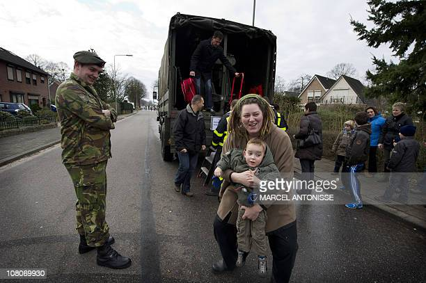 A woman holds a child after an army truck transported villagers of Aijen in Limburg to their houses on January 16 2011 The centre of the village is...