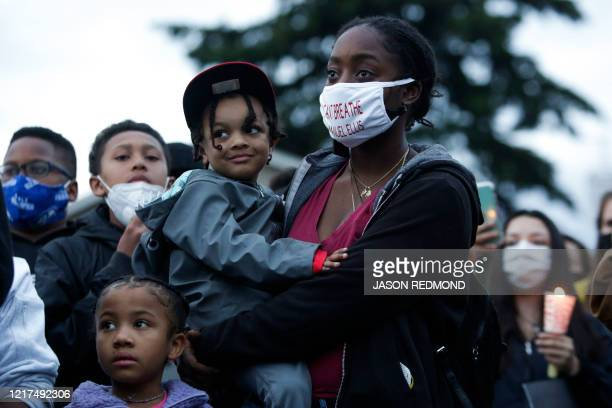 A woman holds a child as family friends and community members attend a vigil at the intersection where Manuel Ellis a 33yearold black man died in...