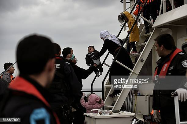 A woman holds a child as migrants and refugees arrive on the Greek island of Lesbos while crossing the Aegean Sea from Turkey on March 2 in Mytilene...
