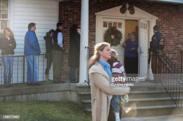A woman holds a child as people line up to enter the Newtown Methodist Church near the the scene of an elementary school shooting on December 14 2012...