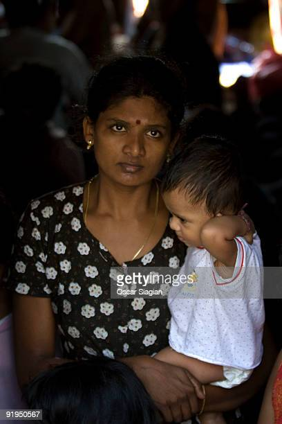 A woman holds a child as Sri Lankan asylum seekers engage in a hunger strike after their boat broke down on the way to Australia's Christmas Island...