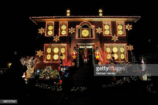 Woman holds a child as they pose for a photo in front of a decorated house on Christmas Eve December 24, 2012 in the Dyker Heights neighborhood of...
