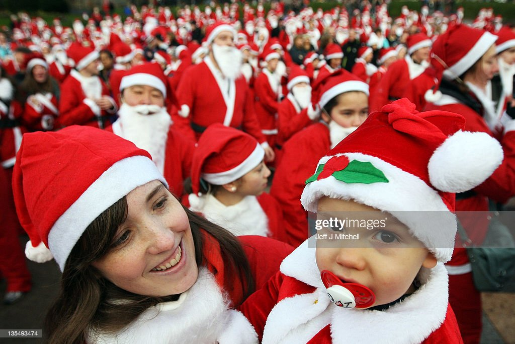 A woman holds a child dressed as Santa Claus as other participants prepare to take part in the Great Edinburgh Santa Run on December 11, 2011 in Edinburgh, Scotland. Around a thousand people took part in the annual fundraising event, with all money raised being donated to the charity 'When You Wish Upon a Star'.