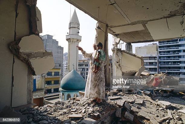 A woman holds a child in a destroyed building near the Ras Mosque This building was destroyed during the West Beirut bombings