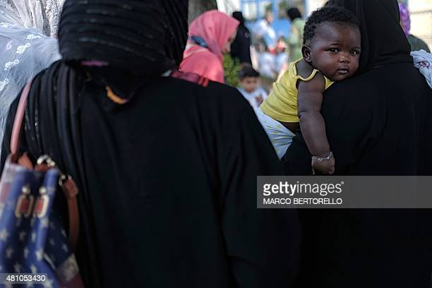 A woman holds a child in her arms as they gather during a celebration of Eid alFitr marking the end of the fasting month of Ramadan in a gymnasium in...