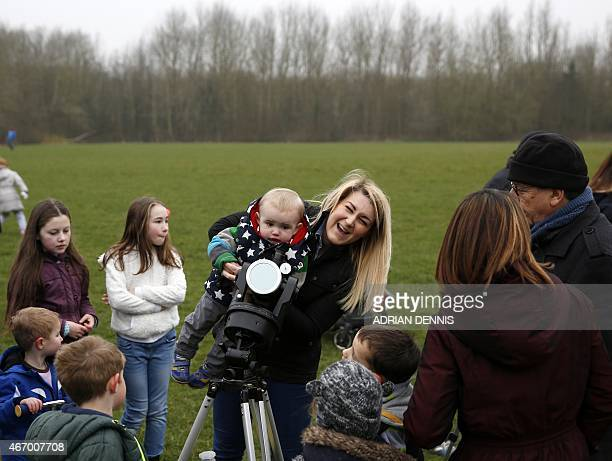 A woman holds a child to look through a telescope to view the solar eclipse at Hatch Warren near Basingstoke some 60 miles southwest of London on...