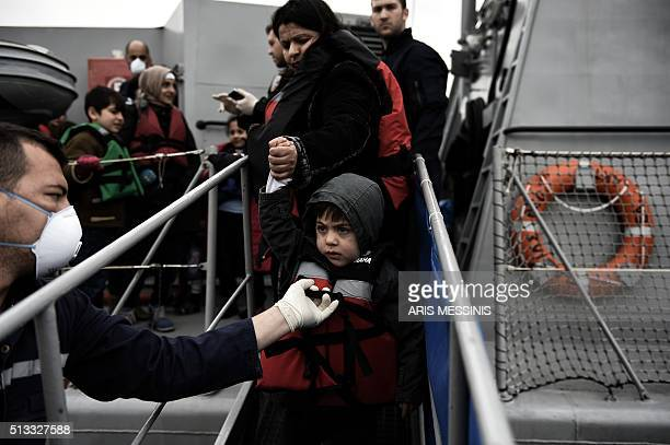 A woman holds a child's hand as migrants and refugees arrive on the Greek island of Lesbos while crossing the Aegean Sea from Turkey on March 2 in...