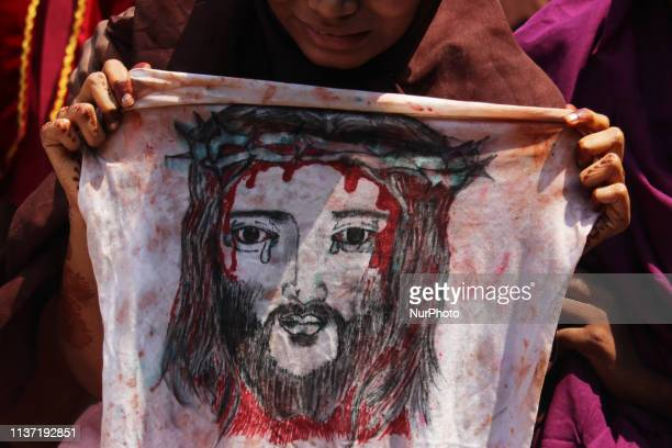 A woman holds a cloth displaying a picture of a Jesus Christ during a reenactment from the Stations of the Cross in Mumbai India on 14 April 2019 The...